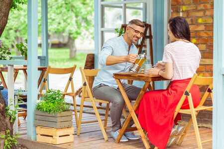 Date night. Happy married couple having a date on a terrace at beautiful summer cafe. Stock Photo