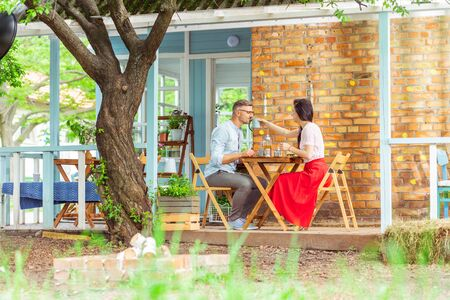 Tea time. Beautiful married couple sitting in a cafe and drinking tea during their date.