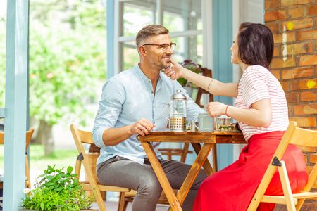 Tender feelings. Beautiful woman gently touching face of a handsome man during their date. Stock Photo