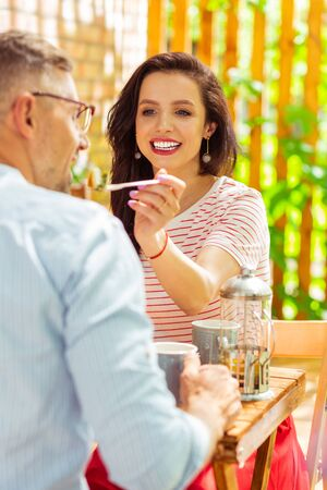 Giving a try. Pretty woman holding a fork sharing her food with her husband. Stock Photo