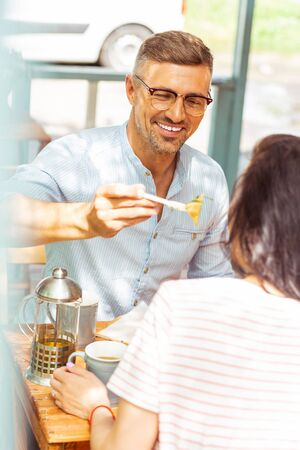 Take a bite. Smiling happy man sharing his food with his beautiful wife sitting in a cafe.