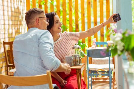 Photographing together. Smiling couple sitting at the cafe table on a date and taking a selfie together.