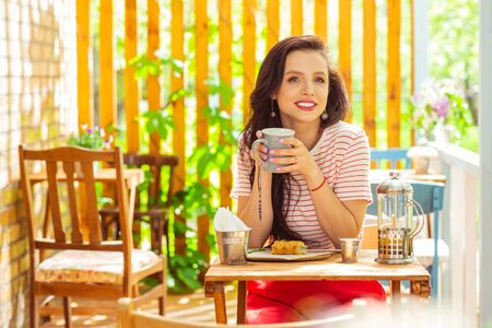 Thinking about future. Smiling thoughtful woman drinking coffee and eating on a terrace of a cute cafe. Stock Photo