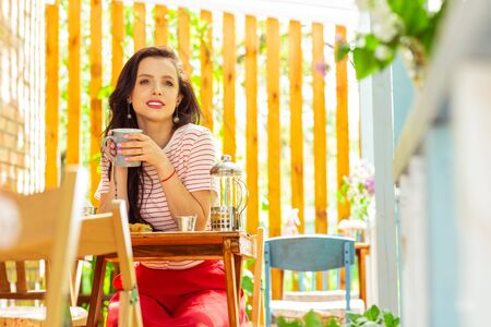 Lonely morning. Thoughtful beautiful woman sitting alone at the cafe table and drinking coffee. Stock Photo
