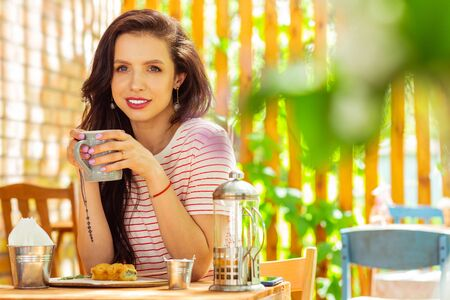 Building plans. Beautiful woman drinking her morning coffee and smiling to her thoughts. Stock Photo