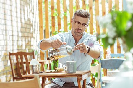 Tea lover. Handsome man in glasses filling his cup with tea sitting at the cafe table.