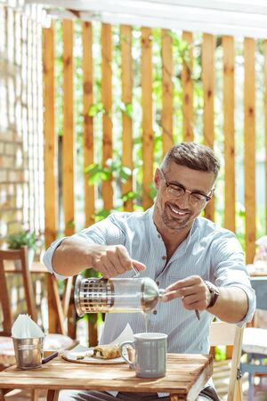 Bright morning. Smiling handsome man drinking tea alone in a summer cafe. Stock Photo
