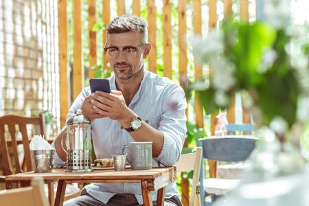 Being aware. Handsome concentrated man at the cafe table reading news on his smartphone.