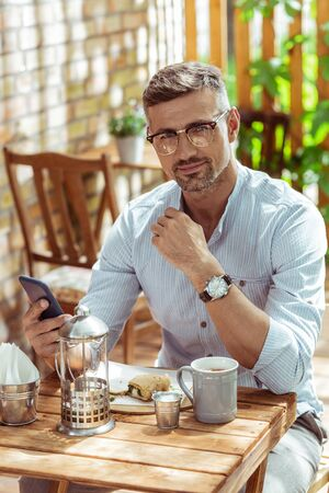 Spending time alone. Handsome man sitting in a summer cafe in the morning and holding his smartphone. Stock Photo