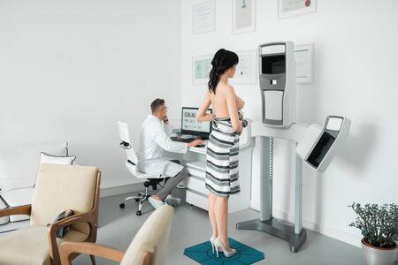 Mujer de cabello oscuro con una investigación de ultrasonido mientras visita al cirujano Foto de archivo