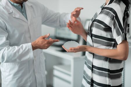 Woman wearing striped dress holding implant for breast while visiting surgeon Banque d'images