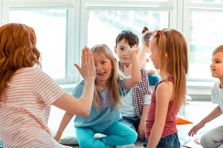 Gut gemacht. Nettes positives Mädchen, das ihre Zunge zeigt, während sie ihrem Lehrer High Five gibt Standard-Bild