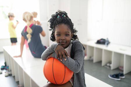 Kleiner Basketballspieler. Fröhliches Schulmädchen, das ihren Basketball an der Bank sitzt und auf ihre Sportstunde wartet.