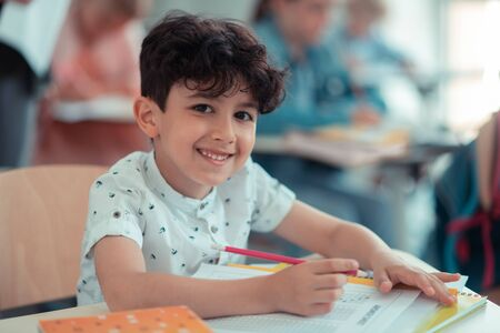 Happy mood. Cheerful pupil sitting at his school desk, writing a test and happily smiling.