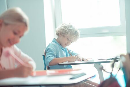 Writing the test. Smiling blond-haired boy writing his test sitting near the window in the class. Stok Fotoğraf