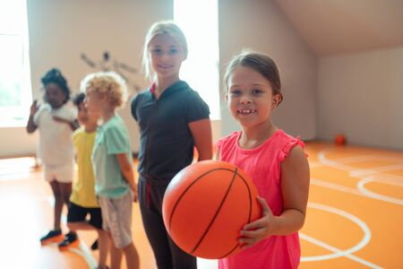 First game. Little smiling schoolgirl with a big basketball in her hands standing near her classmates in gym.
