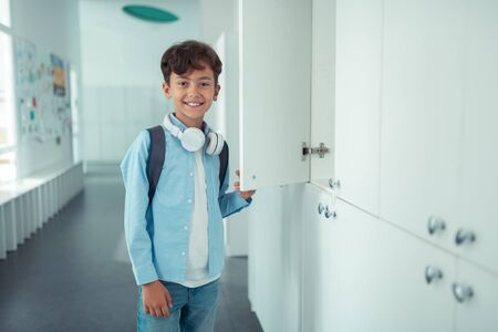 Handsome schoolboy. Handsome schoolboy wearing earphones on neck smiling while standing near school locker Banco de Imagens