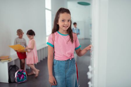 At new school. Dark-eyed girl standing near locker feeling excited before first day at new school