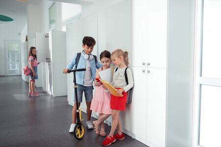 Break from lesson. Stylish good-looking boy and girls standing near lockers while having break from lesson