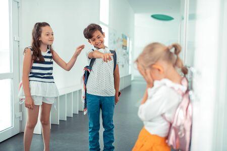 Lachen om meisje. Onbeleefde jongen en meisje lachen om een klein blond meisje dat in de buurt van kluisjes staat