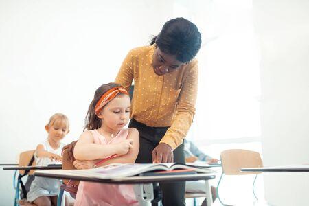 Teacher helping. Professional African-American teacher helping cute little girl sitting at the desk