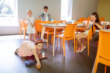 Girl dropping apple. Rude violent girls and boy bullying poor little girl dropping apple on floor