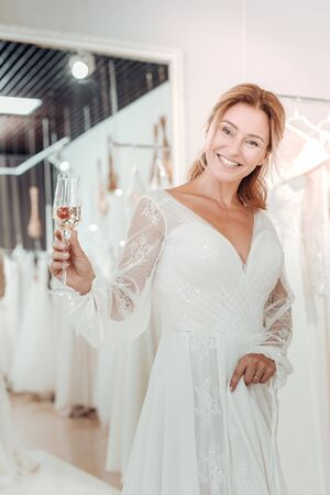 Shopping around. Beautiful smiling woman drinking champagne and trying on white wedding dress in a shop. 写真素材