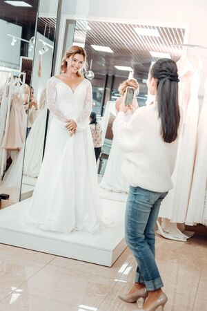 Photographing the dress. Beautiful woman in a wedding dress smiling to her friend taking pictures of her. Фото со стока