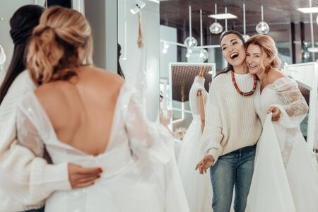 Close friends. Two happy women standing in front of the mirror in a wedding salon and hugging each other. 写真素材