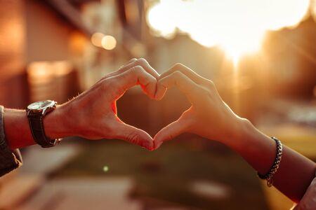 Création de forme de coeur. Joli couple ayant des sentiments forts l'un pour l'autre et les montrant avec les mains connectées