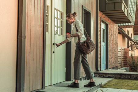 Closing door. Blonde good-looking guy in office outfit carrying leather bag on the shoulder closing his house in the morning