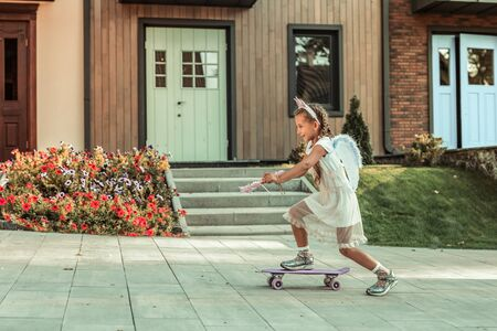 Playing in a neighborhood. Sportive young girl in white dress actively riding on a skateboard in front of her house 免版税图像