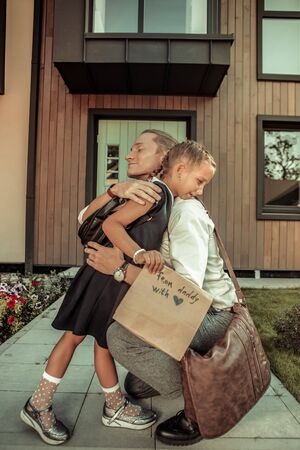 Saying goodbye to father. Caring positive dad tightly hugging young daughter before school day while staying in front of the house