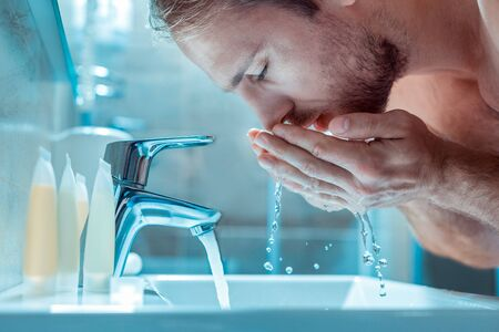 Everyday morning routine . Calm sleepy guy washing face with a clear water while staying in a bathroom