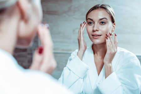 Woman touching face. Appealing lady with red nails applying face cream while wearing white robe