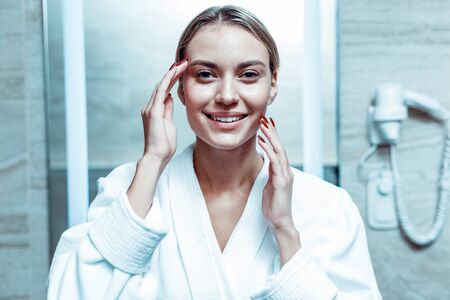 Wearing white robe. Cheerful good-looking lady with tied hair enjoying her flawless skin while staying in a bathroom