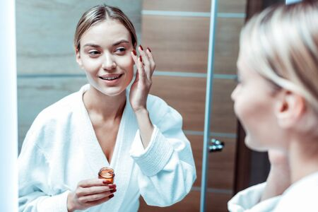 Morning getting ready. Beaming young woman staying in stylish bathroom and carrying glass container with moisturizing cream