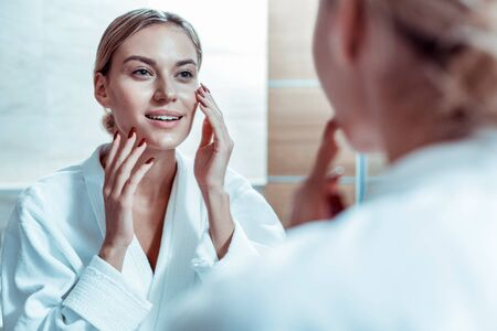 Beautiful lady. Calm blonde woman touching her face and checking state of the skin in bathroom mirror