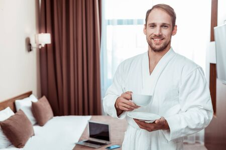 Pleasant morning. Smiling short-haired man drinking morning coffee while wearing white hotel bathrobe