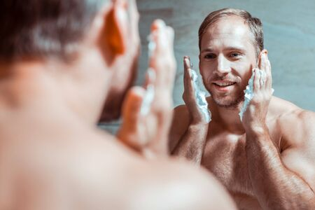 Smoother shaving. Beaming good-looking man preparing face for shaving while having palm covered with foam Stock fotó