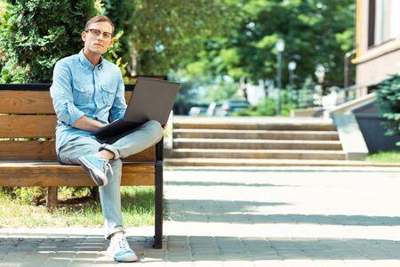 Stylish freelancer. Handsome stylish freelancer wearing glasses sitting on the bench with laptop