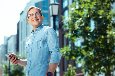 Businessman smiling. Handsome businessman wearing glasses smiling broadly while enjoying weekend walk Stock Photo