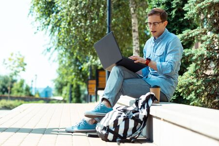 Busy freelancer. Busy freelancer working on laptop while sitting in the park near his backpack