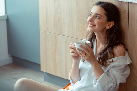 Woman feeling excited. Beautiful young woman feeling excited while drinking coffee in the morning