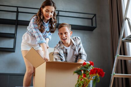Couple unpacking box. Just married couple feeling excited while unpacking box while moving to new house