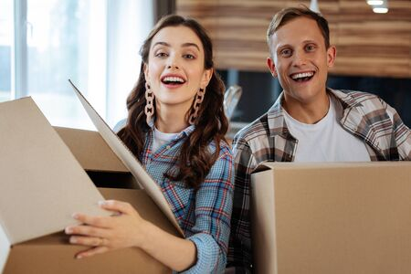 Couple feeling satisfied. Just married couple feeling satisfied moving to new house and holding the boxes
