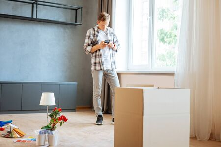 Standing in the room. Dark-haired husband standing in the room while moving to new flat with his wife