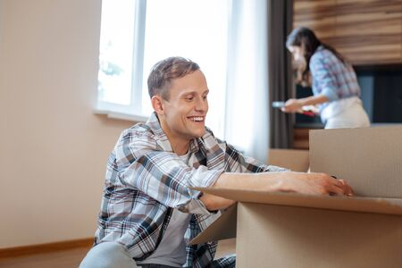 New house. Handsome young husband smiling while unpacking things moving to new house with wife
