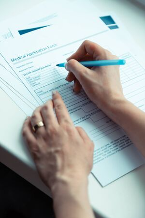 Woman holding pen. Close up of woman holding pen and signing papers buying medical insurance 스톡 콘텐츠