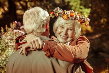 Happy together. Cheerful elderly woman in a flower wreath hugging her husband and smiling in a park.
